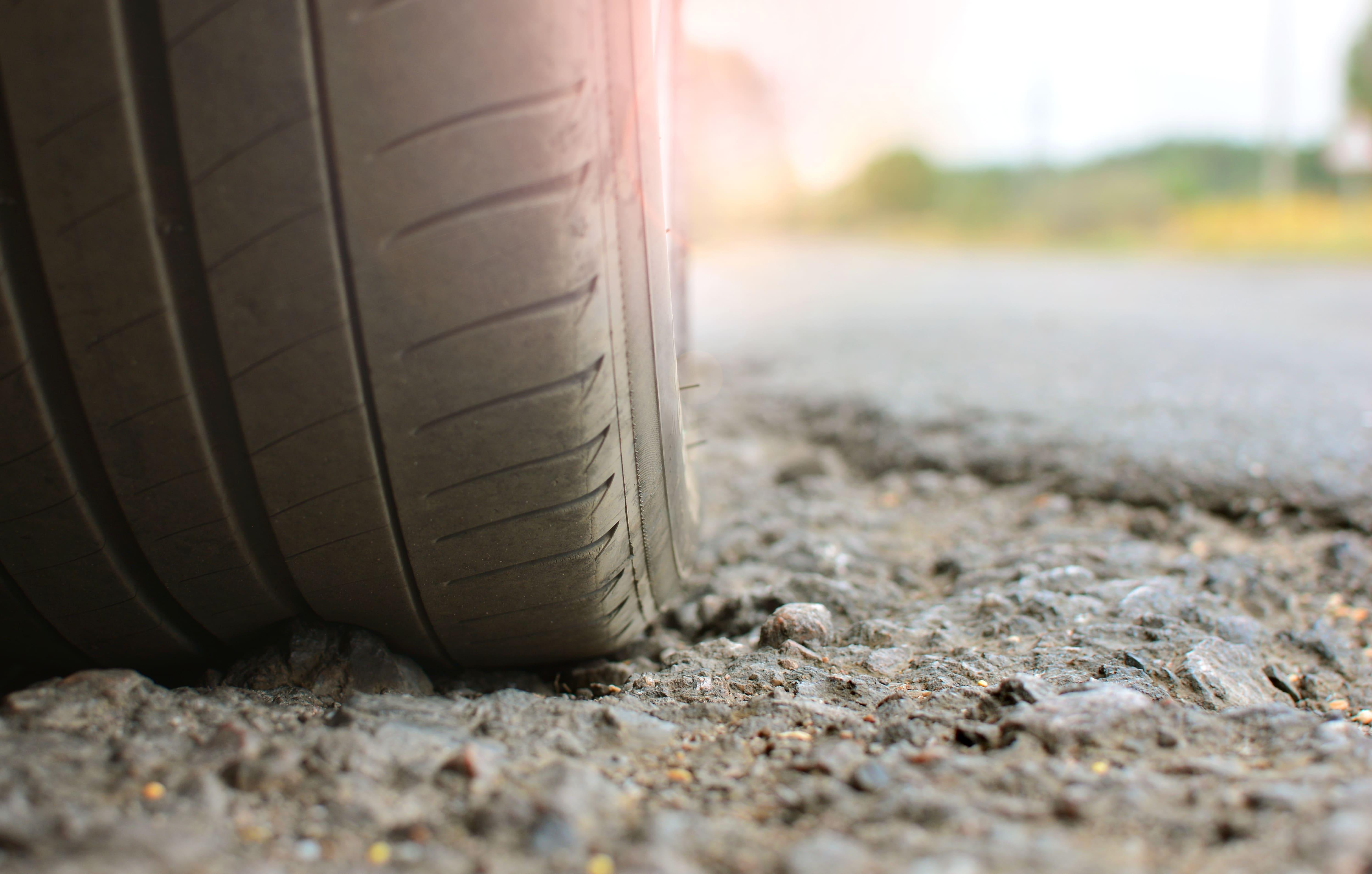 tire on broken asphalt road